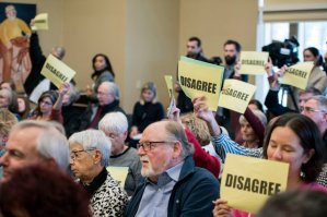 "Audience members hold ""Disagree"" signs at Rep. Jim Sensenbrenner's town hall in Wisconsin (nytimes.com)"